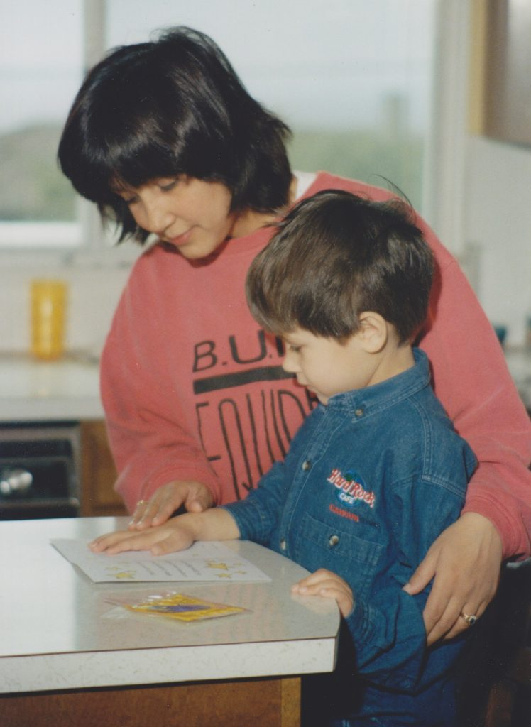 A Mother and young son standing at the kitchen counter pressing the boy's hand on a card, making a handprint footprint keepsakes for parents